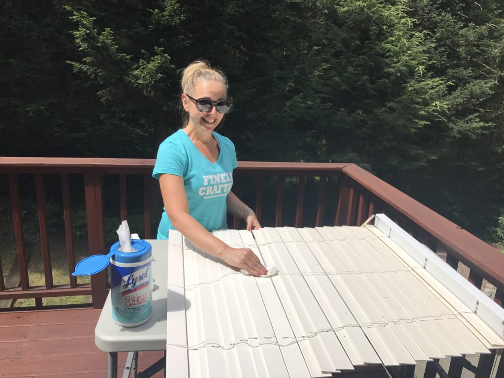 Renee cleaning blinds on her deck to get the house ready.